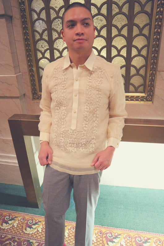 Mark leans back on a gold bar in front of a decorative window. There are marble walls and a green and red carpet. Mark wears his hand embroidered piña silk Barong Tagalog and grey slacks