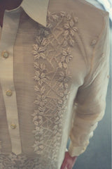 Closeup of the calado hand embroidery on the left side of the piña silk Mark Barong Tagalog. The center button placket, left side of the pointed collar and the left arm and sleeve can be seen
