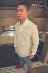 Angled picture of Mark in his hand embroidered piña silk Barong Tagalog, grey slacks and red loafers. He stands at the top of a flight of black stairs. There are light grey marble walls, bannisters, and the lower floor in the background