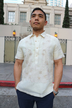 Matt stands in front of the Los Angeles Public Library in his short sleeve hand embroidered jusi Barong Tagalog. Matt also wears a chamisa de chino underneath his barong, blue pants and a wrist watch on his left wrist. The road, sidewalk, gates and trees are also in the background