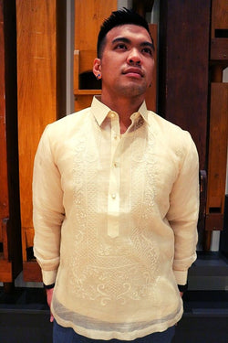 Michael stands in a hand embroidered cocoon Barong Tagalog, chamisa de chino underneath his barong, and grey pants. He stands with his hand in his back pockets looking up and to his left in front of wooden organ pipes.