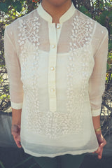 Product photo of the hand embroidered piña silk Mcihelle Barong Tagalog. Michelle wears a white tank top underneath the barong and green pants