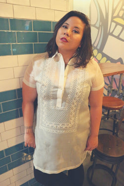 Natalia stands next to a dark green and white tiled pillar and in front of wooden stools, a wooden table and mural in the back. Natalia wears a dress length hand embroidered cocoon Barong Tagalog, a black tank top underneath the barong and black leggings.