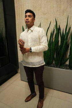 Angled photo of Noel standing in front of tall green plants in a rectangular long grey planter holder. There is beige textured wall behind him and a black wall and mirror to his right. Noel wears a hand embroidered jusi Barong Tagalog, dark maroon slim slacks, blue patterned socks, brown dress shoes, a black wrist watch on his left arm, and a Doom mask ring on his right hand. Noel adjusts his red and yellow bracelets on his right wrist with his left hand in front of him