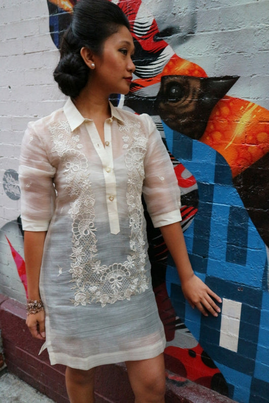 Rachelle stands in her dress length hand embroidered piña silk Barong Tagalog in front of an Audrey Hepburn mural in Little Italy, New York City. She wears a beige tank top and black skirt underneath her barong. She stands at an angle in front of the wall with her left hand touching it.
