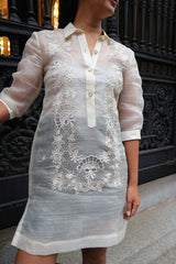 Product photo of the dress length hand embroidered piña silk Rachelle Barong Tagalog. Rachelle wears a beige tank top and black skirt underneath her barong. She stands in front of decorative wrought iron doors in New York City