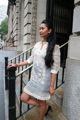 Rachelle stands in her dress length hand embroidered piña silk Barong Tagalog on the steps in front of a building in New York City. She wears a beige tank top and black skirt underneath her barong. She also wears black high heeled shoes. Rachelle has her right hand on the bannister, left hand at her side, her right leg is bent with her right foot resting on a step. Her long hair is draped over her left shoulder and front left side. There is a lion statue and tree in the background