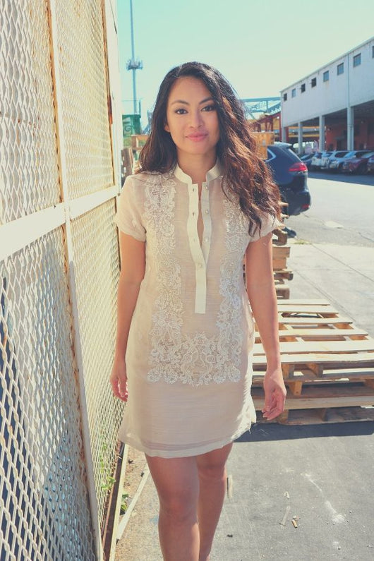 Rechelle walks towards the camera in her dress length hand embroidered piña silk Barong Tagalog. She wears a beige slip dress underneath her barong. She has a white gate to her right, pallets on the ground behind her. There are parked cars, buildings, a bridge and a tower in the background.