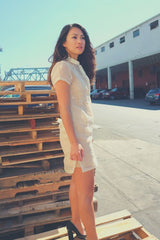 Side view of Rechelle standing on wooden pallets. Rechelle wears a dress length hand embroidered piña silk Barong Tagalog. She wears a beige slip dress underneath her barong. She also wears black high heel shoes. There is a pile of pallets behind Rechelle. There are parked cars, buildings, a bridge and a tower in the background.