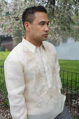 Angled view of Ricky standing in Central Park. Ricky wears a hand embroidered piña silk Barong Tagalog and grey pants. He wears a chamisa de chino underneath his barong. There is a gate, grass, a pond and cherry blossom tree behind him