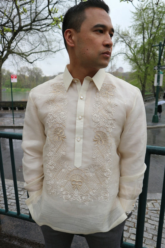 Ricky wears a hand embroidered piña silk Barong Tagalog and grey pants. He wears a chamisa de chino underneath his barong. He stands with his hands in his pockets and he looks to his left. Ricky stands in front of a green gate, there is cobblestone sidewalk, a street and Central Park is behind him. The skies are grey and gloomy