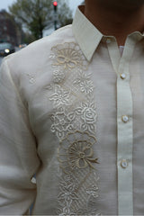 Closeup of the right side of the calado hand embrodery on the piña silk Ricky Barong Tagalog. There is a car, building, tree and traffic light in the background.