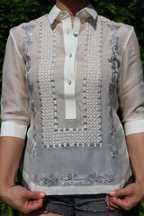 Product picture of the jusi Rissa Barong Tagalog. Rissa pulls down on the bottom of the barong with her hands. She also wears grew shorts. There is green pine in the background
