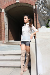 Rissa stands in front of a brick building and stairs and beside a lion statue  at the University of Cincinnati. Rissa wears a blouse length jusi Barong Tagalog, grey shorts and thigh high light brown boots