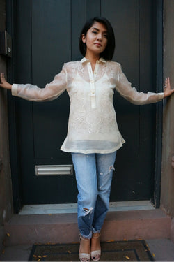 Robin stands in front of a dark green door in her hand embroidered piña silk Barong Tagalog, white tank top underneath her barong, blue jeans and tan open toe shoes. She stands with her hands reaching and touching the sides of the doorway