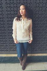 Roe stands in front of a decorated iron vent in her hand embroidered piña silk Barong Tagalog, white tank top underneath her barong, blue jeans, knee high brown boots and gold bracelet on her right hand. Roe stands with her back to the vent and looks to her right. Her hands hold the bottom of her barong