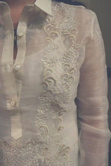 Closeup photo of the right side of the calado hand embroidery on the piña silk Roe Barong Tagalog. Roe wears a white tank top and necklace underneath her barong.
