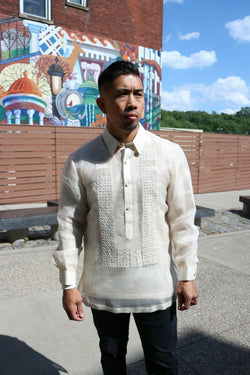 Ronnie stands in his hand embroidered piña silk Barong Tagalog, a chamisa de chino underneath his barong and black pants in front of stone benches, a fence, a building with a mural, trees and the sky in the background