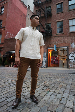 Upward photo of Ryan standing on a cobblestone road with downtown NYC buildings behind him. Ryan wears a short sleeve hand embroidered jusi Barong Tagalog, a chamisa de chino underneath his barong, brown slacks and dark brown shoes