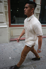 Side view of Ryan walking on the sidewalk with a building with windows to his right. Ryan wears a short sleeve hand embroidered jusi Barong Tagalog, a chamisa de chino underneath his barong, brown slacks, dark brown shoes and a silver watch on his left wrist