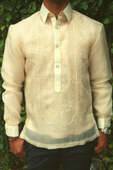 Product photo of the hand embroidered cocoon Ryan Barong Tagalog. Ryan wears a chamisa de chino underneath his barong, blue navy slacks, a silver watch on his left wrist and a bracelet on his right wrist. Ryan stands in front of a green leaf covered wall with his thumbs hanging onto his pants pockets
