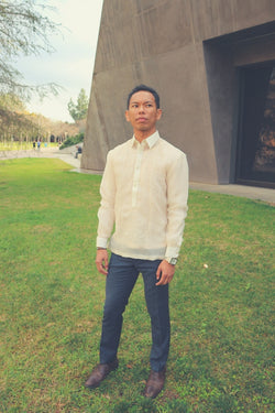 Ryan stands on a grass lawn with a cement structure behind him. There are paved walkways, trees and people walking and sitting in the distant background. Ryan wears a hand embroidered cocoon Barong Tagalog, a chamisa de chino underneath his barong, navy slacks, brown shoes and a silver watch on his left wrist. Ryan stands straight at an angle as he looks to his left