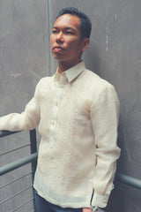 Photo of Ryan from the hips up. Ryan standing at an angle looking straight ahead with his back to a grey wall, his right arm resting on grey handrails and his left hand in his pocket. Ryan wears a hand embroidered cocoon Barong Tagalog. Ryan wears a chamisa de chino underneath his barong, navy slacks and a silver wrist watch on his left wrist.