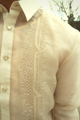 Closeup shot of the upper right calado hand embroidery on the cocoon Ryan Barong Tagalog. Ryan wears a chamisa de chino underneath his barong. There is a tree, building and the sky in the background