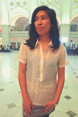 Ryann stands in main hall of DC Union Station in her jusi Barong Tagalog, tank top underneath her barong and grey skirt.