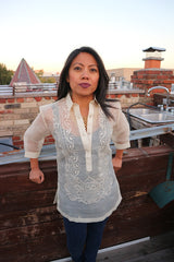 Sarahlynn stands in her hand embroidered piña silk Barong Tagalog, black tank top underneath her barong, and dark blue jeans. She stands leaning back with her hands resting on a wooden wall. She is on a rooftop, and a brick wall, sink, chimney, other rooftops, trees and the sky is in the background