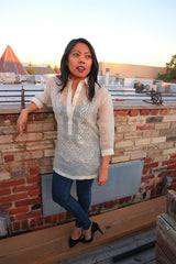 Sarahlynn stands in her hand embroidered piña silk Barong Tagalog, black tank top underneath her barong, dark blue jeans, and black high heel shoes. She stands on a wodden plank, leaning back with her right elbow resting on the brick wall behind her. She is on a rooftop, and other rooftops, chimneys, a tree and the sky are in the background