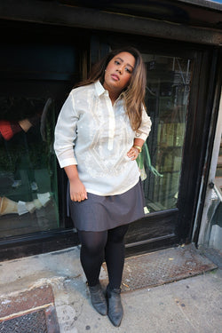 Stephanie stands in her hand embroidered jusi Barong Tagalog, a black 3/4 sleeve top underneather her barong, grey skirt, black leggings and grey boots. She stands with her back leaning on a store window behind her, her head tilted to her left, left hand on her hip and right hand at her side