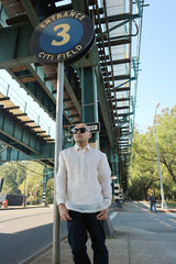Upward photo of Steven leaning next to a street sign that says Entrance 3 Citi Field. Steven stands on the sidewalk on Roosevelt Avenue under the elevated tracks of the 7 train in Flushing. Steven wears a hand embroidered piña silk Barong Tagalog, a chamisa de chino underneath his barong, dark jeans and black sunglasses. He stands with his hands hanging off his pockets. There are streets, a pedestrian, trees, a street light, other street signs, and the blue sky in the background