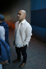 Steven wears a hand embroidered piña silk Barong Tagalog, a chamisa de chino underneath his barong, dark jeans and brown dress shoes. He stands with his hands in his pockets on the sidewalk behind a couple people on a line. There is a concrete wall, part of which is painted blue, behind him.
