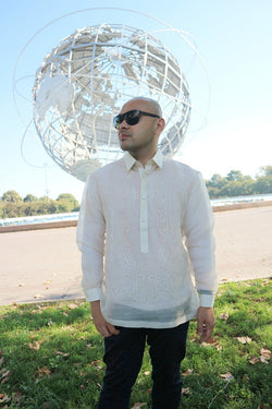Steven stands in Flushing Meadow Park in front of the Unisphere. Steven wears a hand embroidered piña silk Barong Tagalog, a chamisa de chino underneath his barong, dark jeans and black sunglasses. He stands on the grass and there are trees and the blue sky in the background