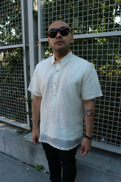 Steve stands in his short sleeve hand embroidered jusi Barong Tagalog, a chamisa de chino underneath his barong, dark jeans, black sunglasses and black bracelet on his left wrist. He stands in front of a grid gate with trees behind it