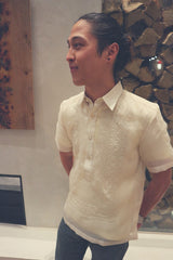 Angled photo of Tiger standing with his hands behind his back and a smirk on his face in front of a modern fireplace wall in his hand embroidered cocoon Barong Tagalog, a chamisa de chino underneath his barong and dark jeans.