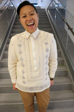 Tonilyn stands at the bottom of a grey stairwell. Tonilyn wears a jusi Barong Tagalog, a chamisa de chino underneath the barong, light brown khaki pants and a beaded bracelet. Tonilyn's hands are in the pockets and Tonilyn is smiling with mouth open