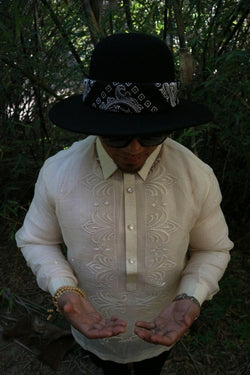 Photo of top half of Zar standing looking down at his palms facing up held in front of his stomach. Zar wears a hand embroidered piña silk Barong Tagalog, chamisa de chino underneath his barong, black sunglasses and black hat with black bandana tied around the hat, beaded bracelet on right wrist and watch on left wrist. There are tree branches and leaves in the dark background