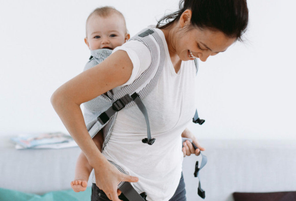 Mom carries happy baby in Weego Original Infant Carrier