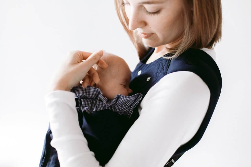 Mother holding newborn in Weego ORIGINAL baby carrier