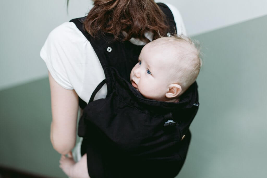 Young mother carrying baby on her back in Weego Baby Carrier