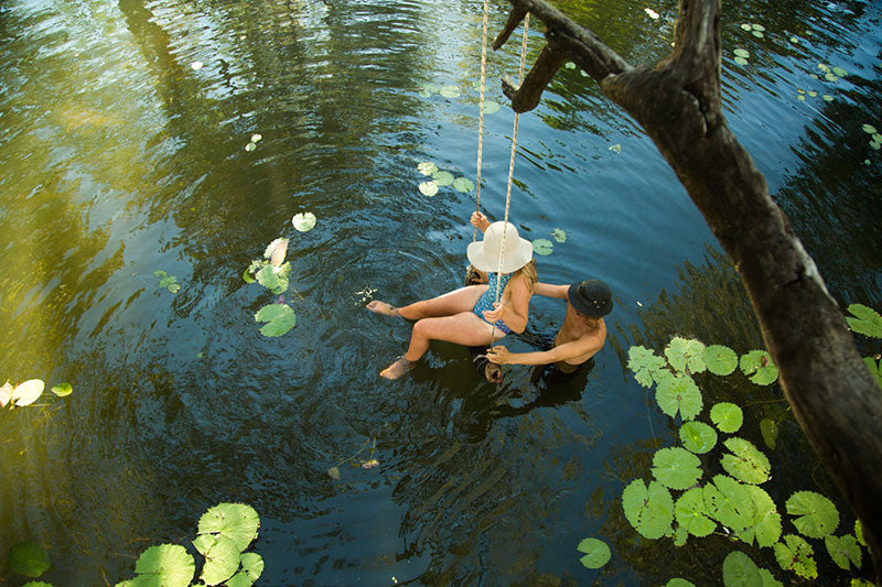swinging over water with hats