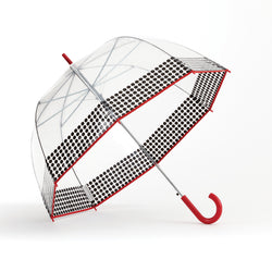 side view of a push button auto open dome-shaped clear bubble umbrella printed with a black polka dot border and trimmed with bright red fabric binding around the transparent canopy and a high gloss red curved plastic crook handle with a matching shiny red ferrule.