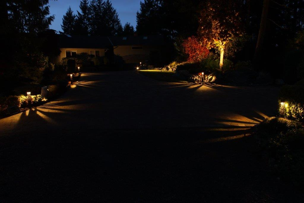 Long driveway lit at night using landscape lights.