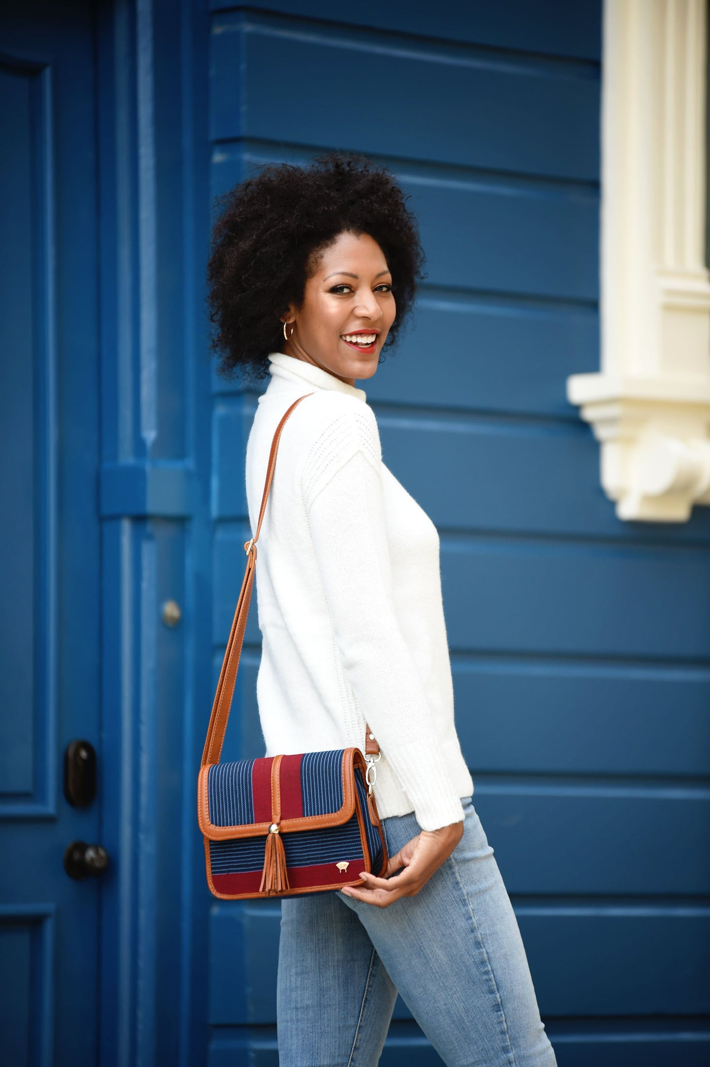African-American model smiling at the camera, carrying an Olori Tola Maiden Crossbody bag in brown