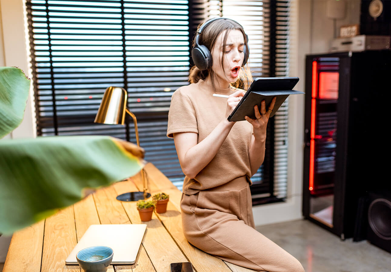 A woman wearing over-ear headphones and leaning against a desk uses the Apple Pencil to make a note on her iPad.