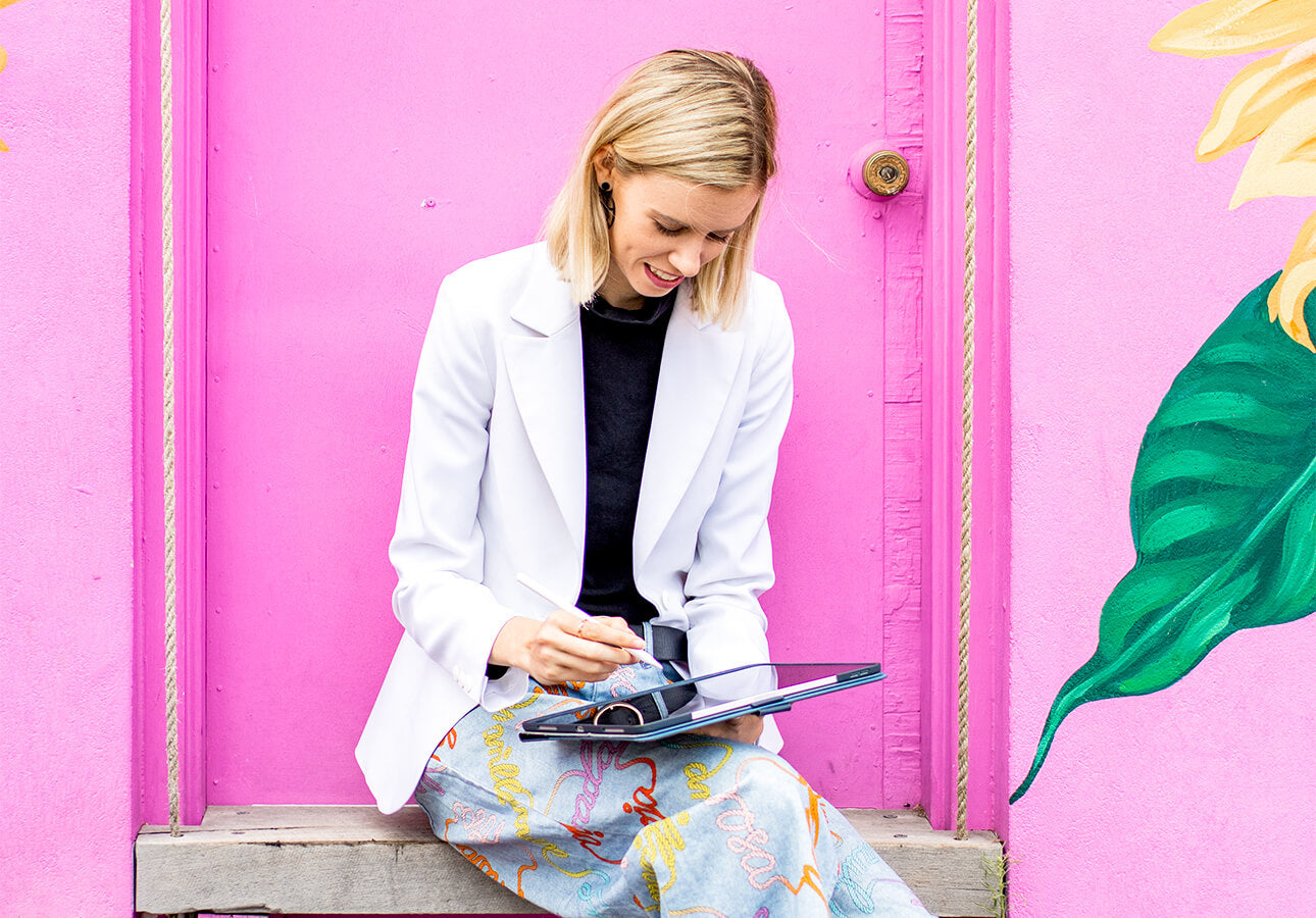 A woman in business attire makes notes with her iPad and Apple Pencil.