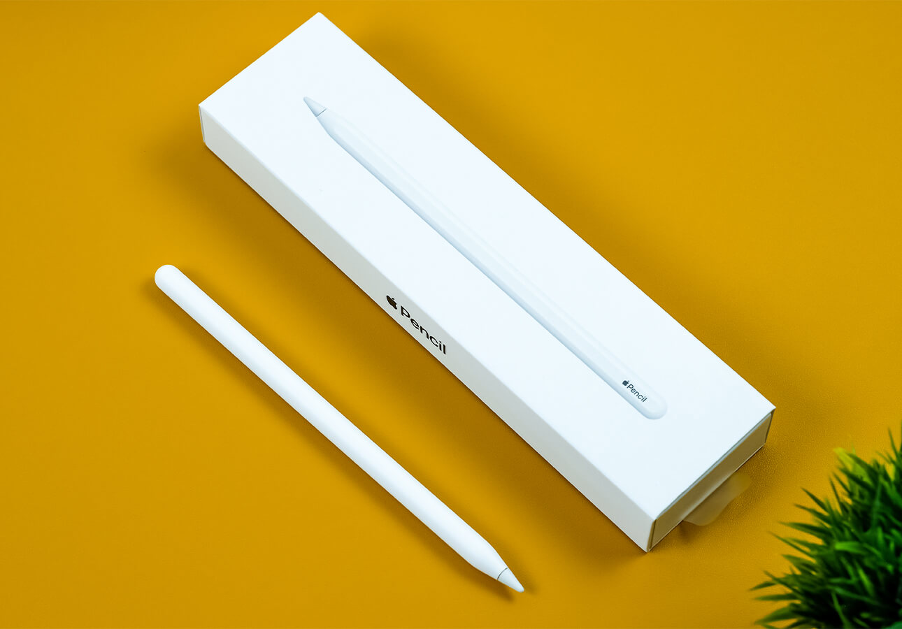 An Apple Pencil (2nd Generation) sits on a yellow table beside its original packaging.