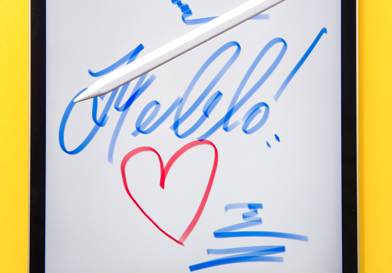 """An iPad screen featuring a handdrawn heart and the word """"Hello."""" An Apple Pencil rests on top of the         screen."""